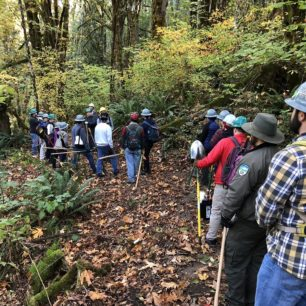 Volunteers listening to trail crew lead describe the work to be done