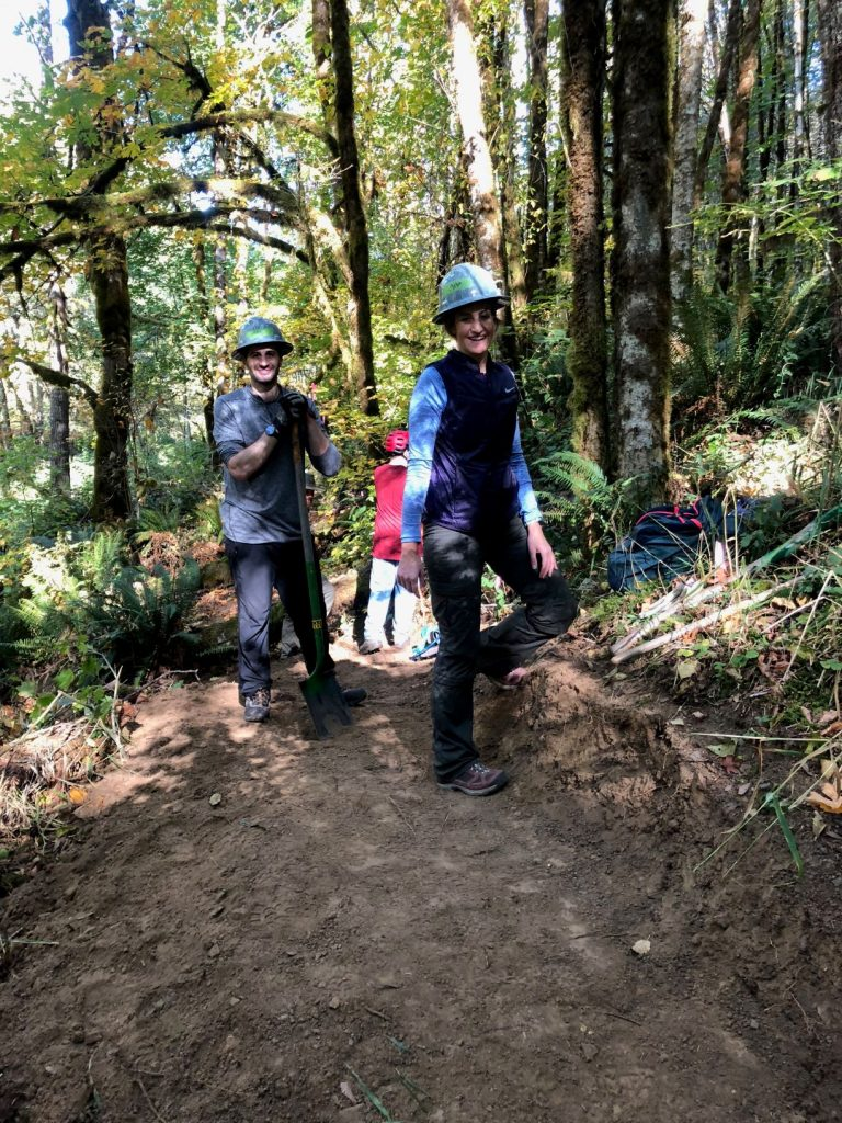 Two volunteers showing off their hard freshly benched trail.